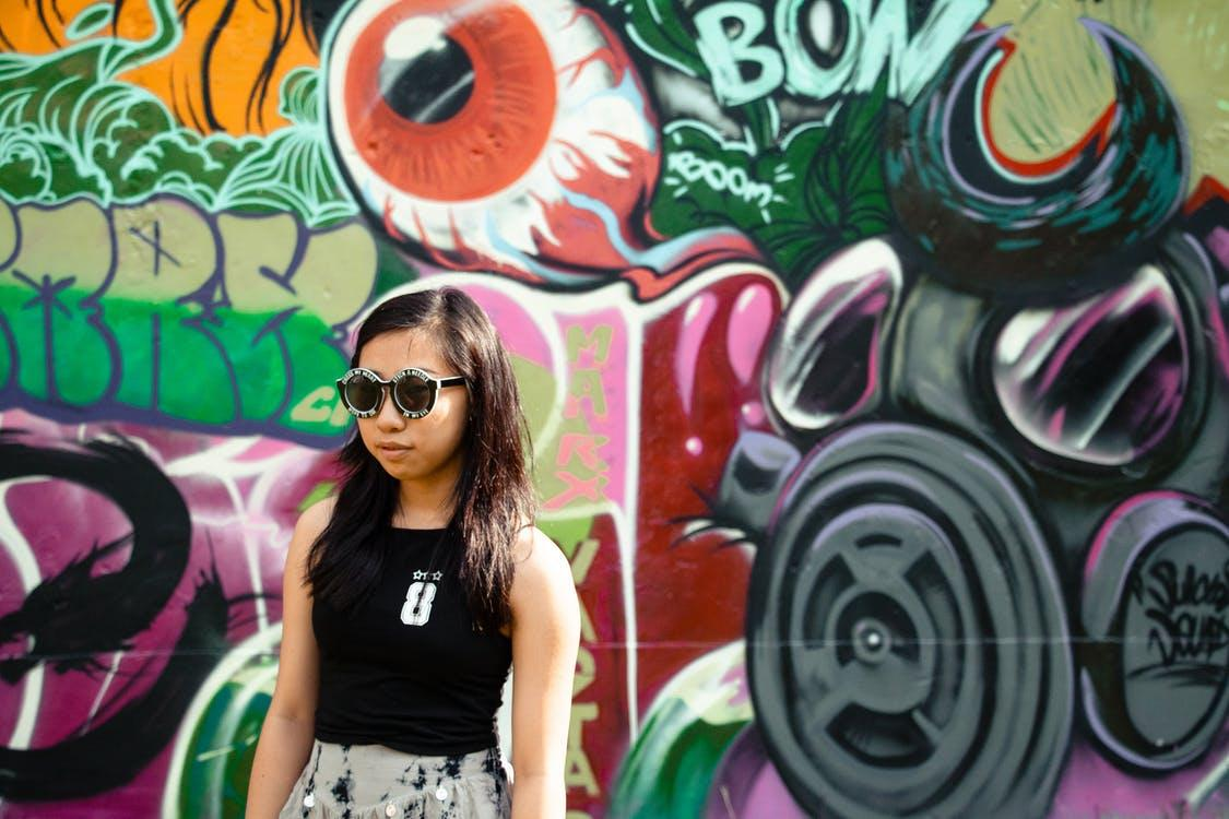 Woman In Black Top And Black Sunglasses Standing Beside Graffiti Wall